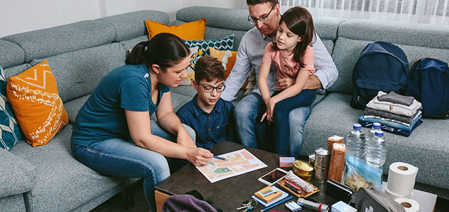 Family sits together on couch with their emergency kit materials